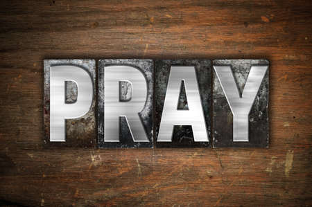 tabernacle: The word Pray written in vintage metal letterpress type on an aged wooden background. Stock Photo