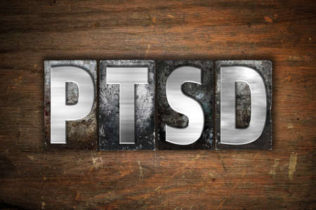 traumatic: The word PTSD written in vintage metal letterpress type on an aged wooden background. Stock Photo