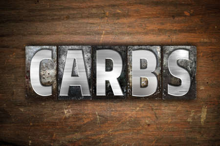 carbs: The word Carbs written in vintage metal letterpress type on an aged wooden background. Stock Photo