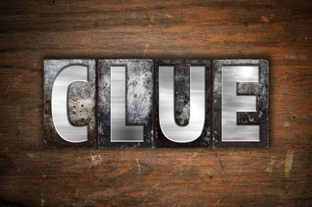 crime solving: The word Clue written in vintage metal letterpress type on an aged wooden background.