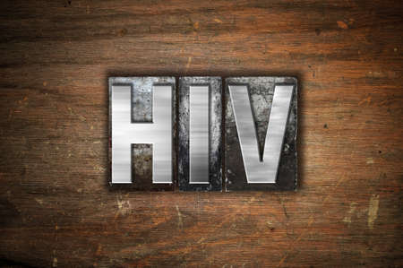 sexually transmitted disease: The word HIV written in vintage metal letterpress type on an aged wooden background.