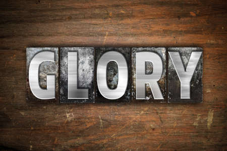 reverent: The word Glory written in vintage metal letterpress type on an aged wooden background. Stock Photo