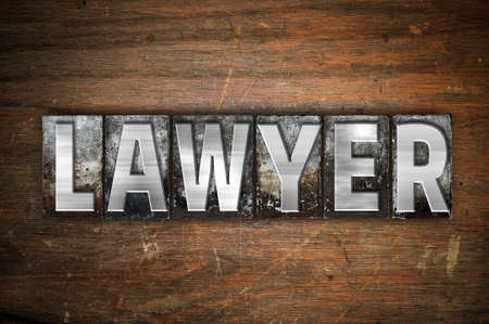The word Lawyer written in vintage metal letterpress type on an aged wooden background.