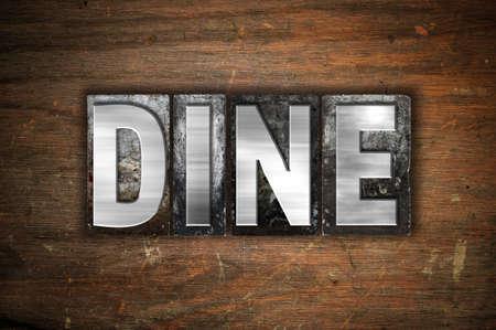 """Het woord """"Dineren"""" geschreven in vintage metalen boekdruk soort op een oude houten achtergrond."""