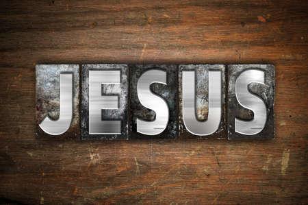 Het woord 'Jezus' is geschreven in vintage metalen letterpress type op een oude houten achtergrond. Stockfoto