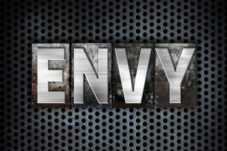 covet: The word Envy written in vintage metal letterpress type on a black industrial grid background.