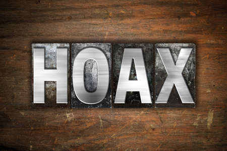hoax: The word Hoax written in vintage metal letterpress type on an aged wooden background.