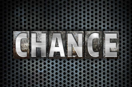unplanned: The word Chance written in vintage metal letterpress type on a black industrial grid background. Stock Photo