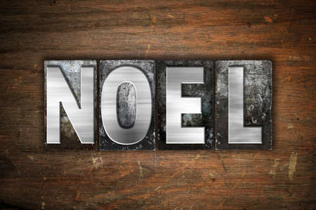 hymn: The word Noel written in vintage metal letterpress type on an aged wooden background.