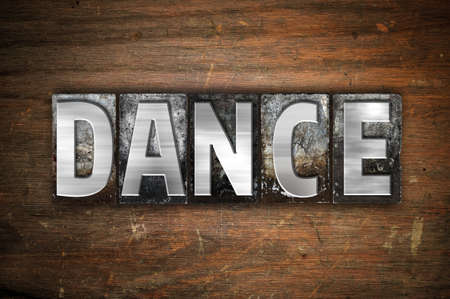 The word Dance written in vintage metal letterpress type on an aged wooden background.
