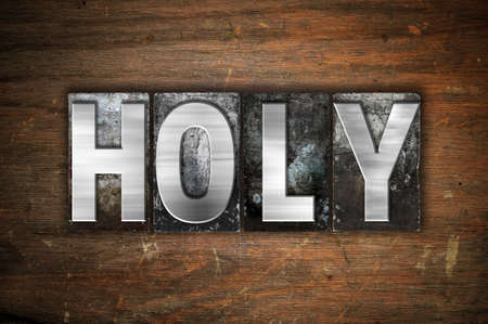 sanctified: The word Holy written in vintage metal letterpress type on an aged wooden background. Stock Photo