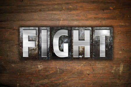bout: The word Fight written in vintage metal letterpress type on an aged wooden background.