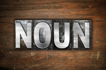 noun: The word Noun written in vintage metal letterpress type on an aged wooden background.
