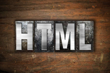 html: The word HTML written in vintage metal letterpress type on an aged wooden background.