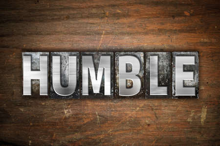 The word Humble written in vintage metal letterpress type on an aged wooden background.
