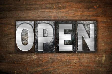 """Het woord """"Open"""" geschreven in vintage metalen boekdruk soort op een oude houten achtergrond."""