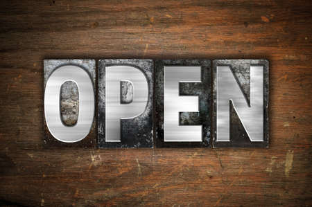 unopen: The word Open written in vintage metal letterpress type on an aged wooden background.