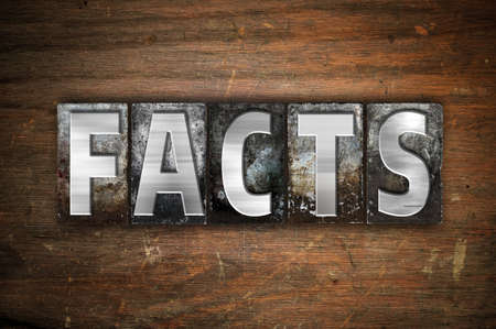 The word Facts written in vintage metal letterpress type on an aged wooden background.