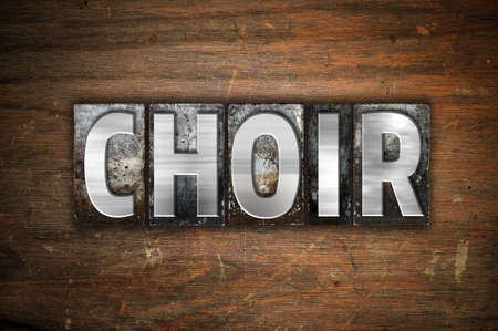 The word Choir written in vintage metal letterpress type on an aged wooden background.