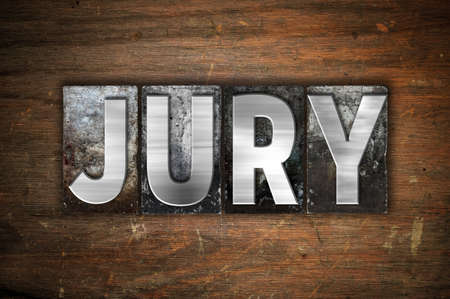 The word Jury written in vintage metal letterpress type on an aged wooden background.