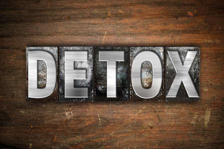 """Das Wort """"Detox"""" geschrieben in Vintage-Metall-Buch-Typ auf einem gealterten hölzernen Hintergrund."""