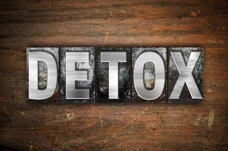 "The word ""Detox"" written in vintage metal letterpress type on an aged wooden background."