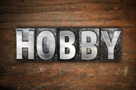 The word Hobby written in vintage metal letterpress type on an aged wooden background. Imagens