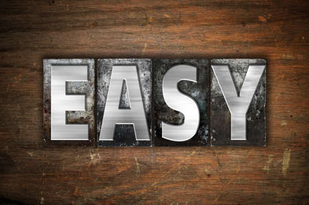 The word Easy written in vintage metal letterpress type on an aged wooden background.