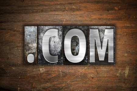 dot com: The word Dot com written in vintage metal letterpress type on an aged wooden background. Stock Photo