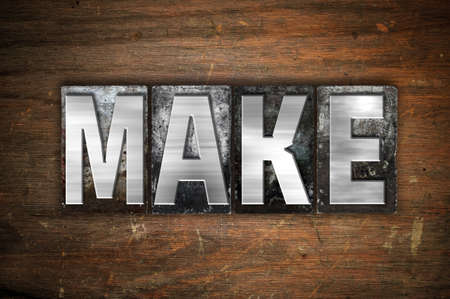 The word Make written in vintage metal letterpress type on an aged wooden background.