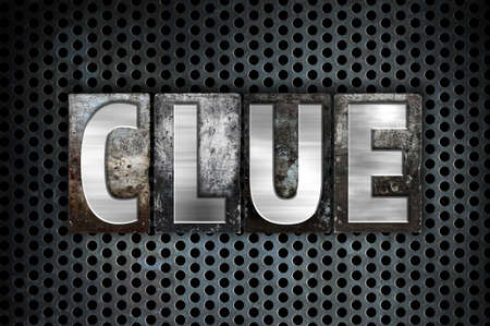 The word Clue written in vintage metal letterpress type on a black industrial grid background. Stock Photo