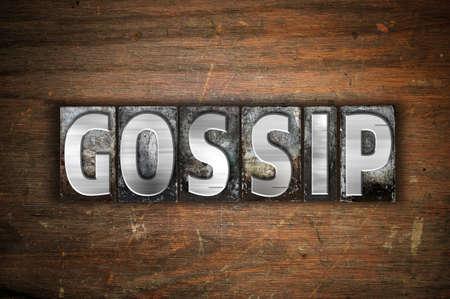 The word Gossip written in vintage metal letterpress type on an aged wooden background.