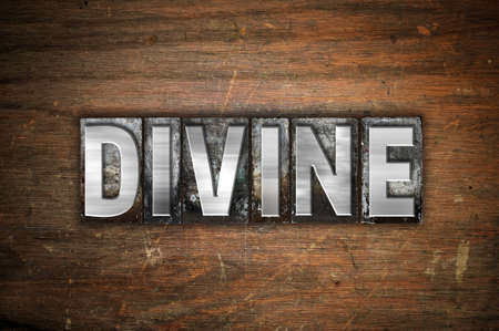 The word Divine written in vintage metal letterpress type on an aged wooden background. Stock Photo