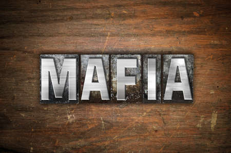 The word Mafia written in vintage metal letterpress type on an aged wooden background. Imagens