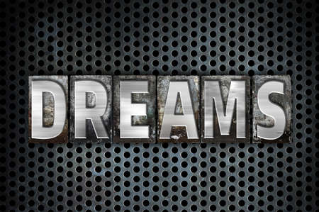 The word Dreams written in vintage metal letterpress type on a black industrial grid background. Stock Photo
