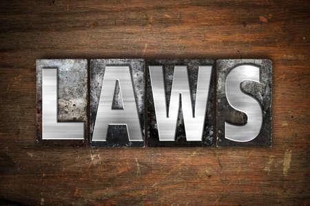 """edicto: La expresión """"leyes"""" escrito en tipo de cosecha tipografía de metal sobre un fondo de madera envejecida."""