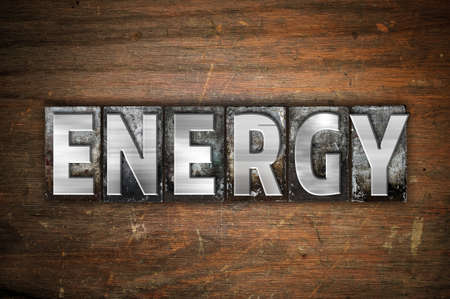 energize: The word Energy written in vintage metal letterpress type on an aged wooden background.