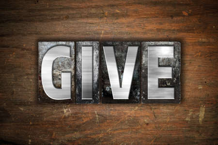 endow: The word Give written in vintage metal letterpress type on an aged wooden background. Stock Photo