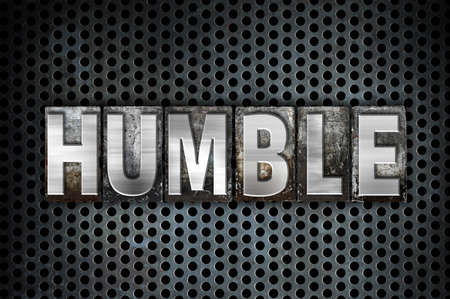 The word Humble written in vintage metal letterpress type on a black industrial grid background.