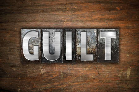 guilt: The word Guilt written in vintage metal letterpress type on an aged wooden background.