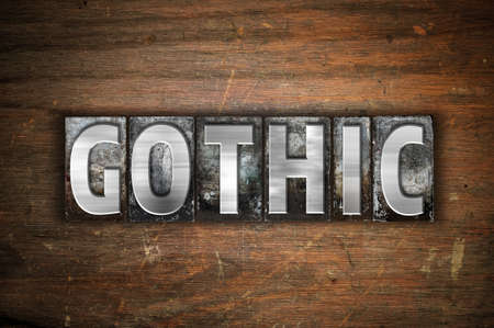 gothic revival style: The word Gothic written in vintage metal letterpress type on an aged wooden background.