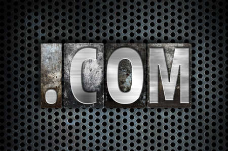 dot com: The word Dot com written in vintage metal letterpress type on a black industrial grid background.