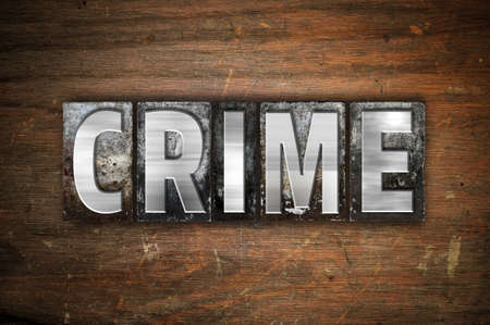 armed robbery: The word Crime written in vintage metal letterpress type on an aged wooden background. Stock Photo