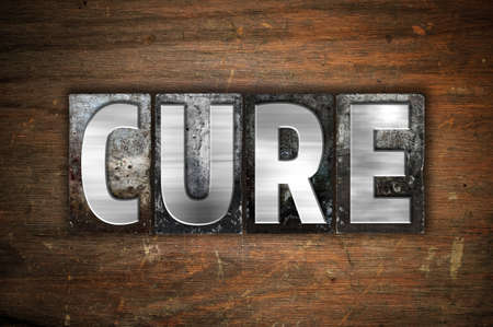 clinical trial: The word Cure written in vintage metal letterpress type on an aged wooden background. Stock Photo