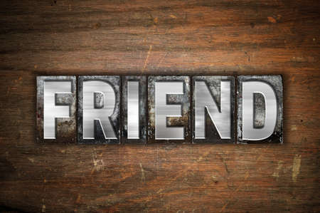 soul mate: The word Friend written in vintage metal letterpress type on an aged wooden background. Stock Photo