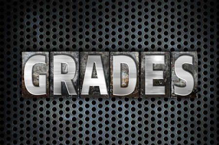 grades: The word Grades written in vintage metal letterpress type on a black industrial grid background. Stock Photo