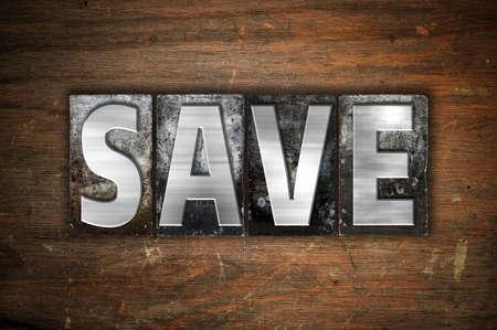"""Het woord """"Save"""" geschreven in vintage metalen boekdruk soort op een oude houten achtergrond."""