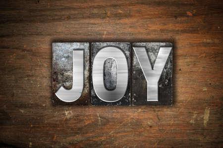 "The word ""Joy"" written in vintage metal letterpress type on an aged wooden background."