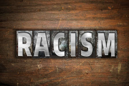 bigotry: The word Racism written in vintage metal letterpress type on an aged wooden background.