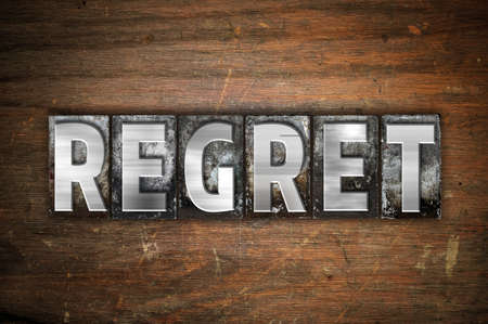 regret: The word Regret written in vintage metal letterpress type on an aged wooden background. Stock Photo